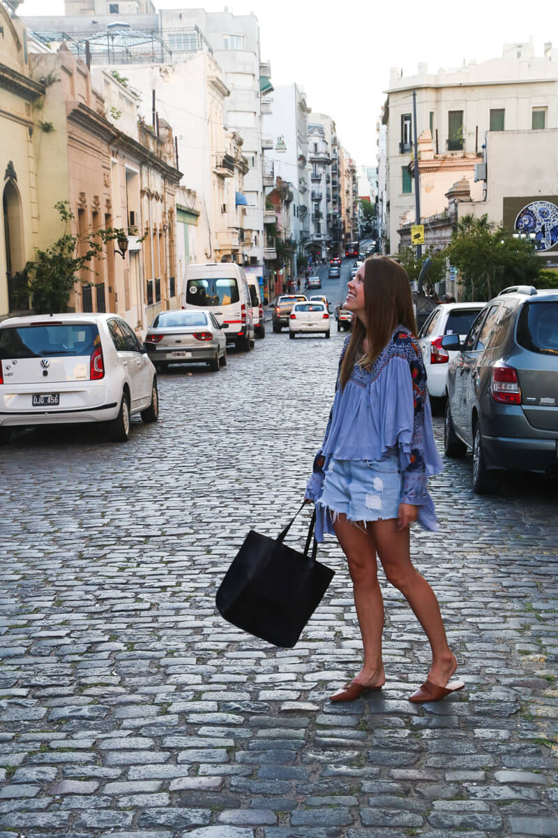 A woman stands on a cobblestone street next to cars and historic one story buildings in Buenos Aires