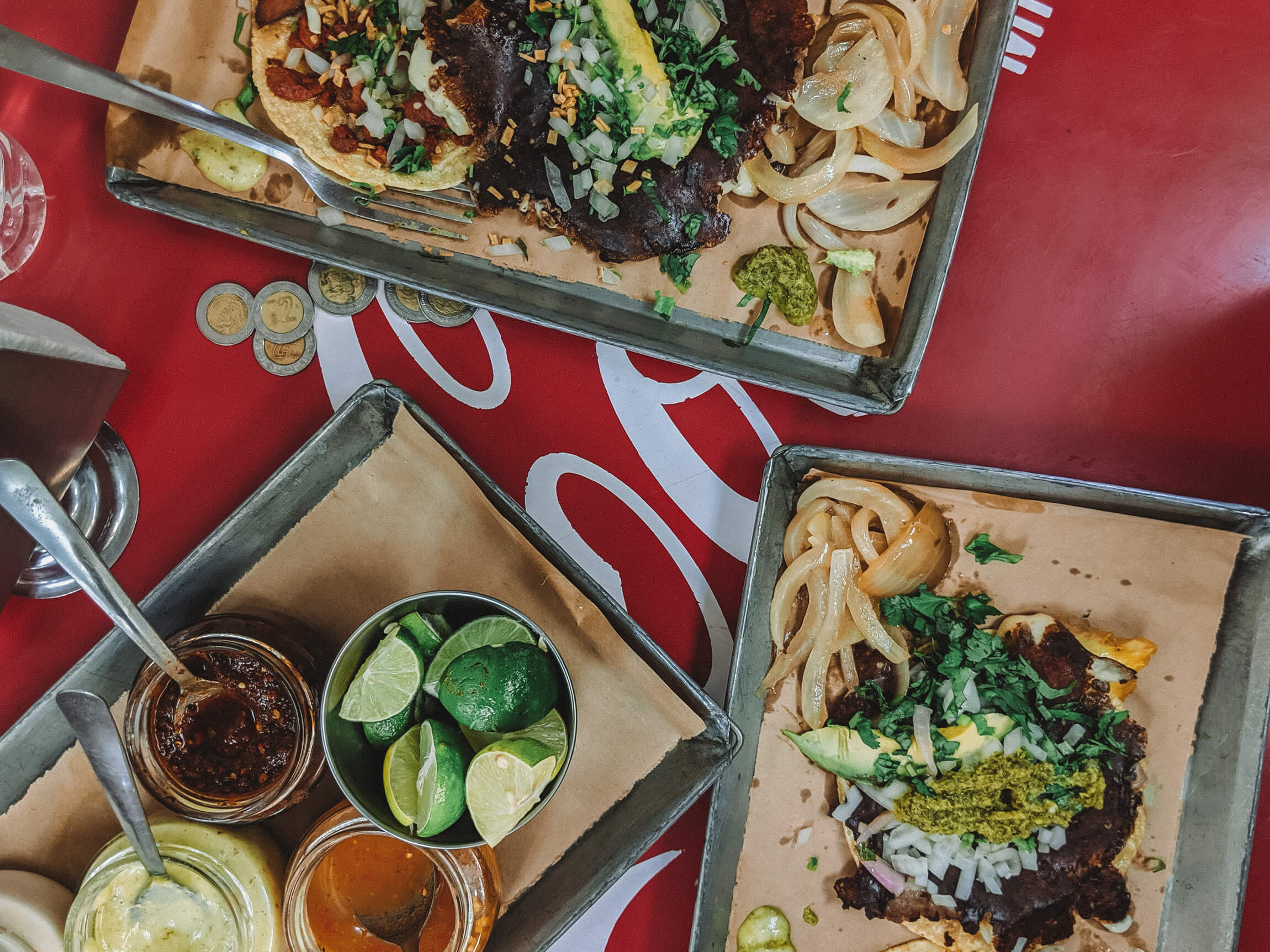 A red coca cola branded table with three trays holding tacos and hot sauces in a Mexico City taco shop