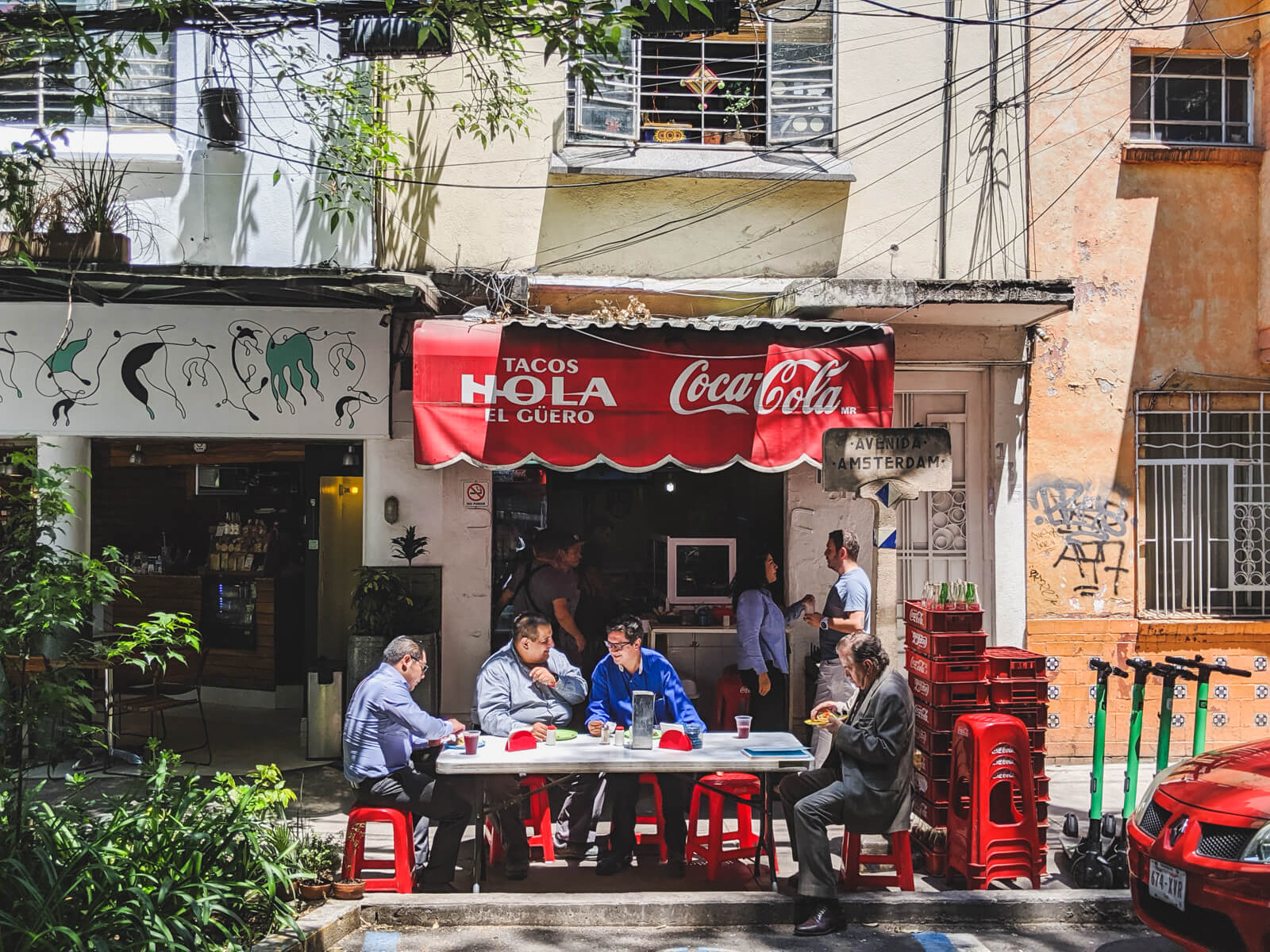 Four men sit around a table in front of a taqueria in Mexico City