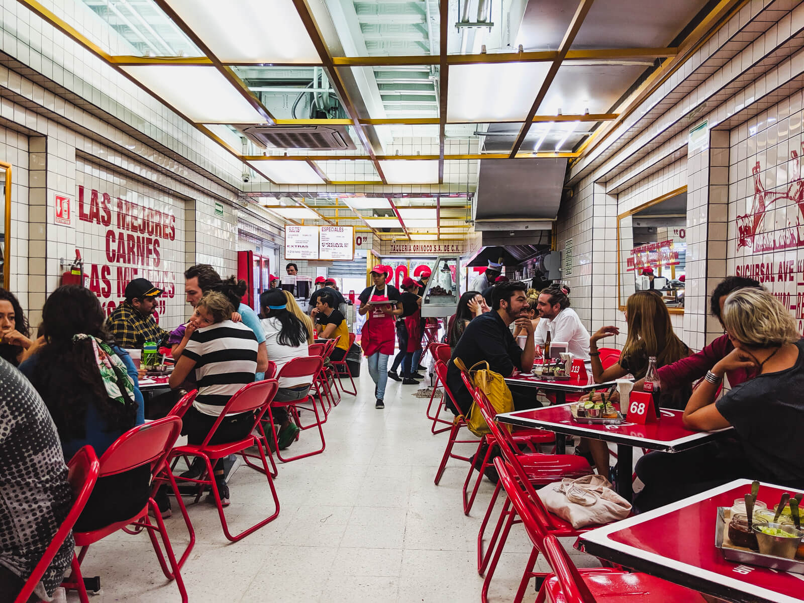 A restaurant filled with red folding chairs and tables with white tiled walls is filled with customers