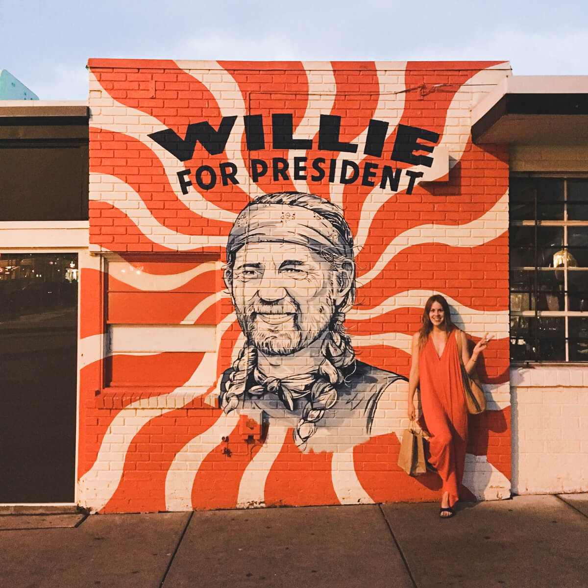 A woman stands on the sidewalk in front of a mural of Willie Nelson in Austin Texas
