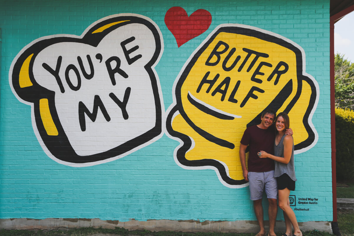 One day in Austin isn't complete without hunting down the murals, a couple stands in front of a turquoise wall with two slices of toast and butter painted with the words You're My Butter Half painted on the bread