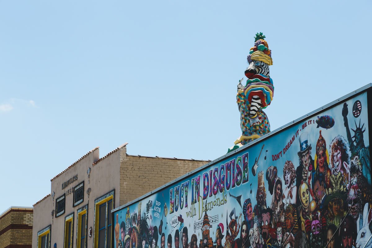 A zebra statue dressed up in a dress and a fruit hat stands on top of a storefront in Austin Texsa