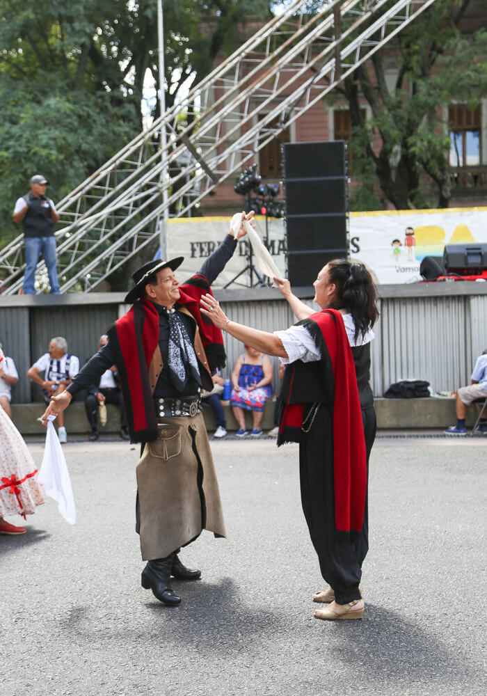A man and woman dance in an outdoor market in Buenos Aires dressed in traditional gaucho clothing