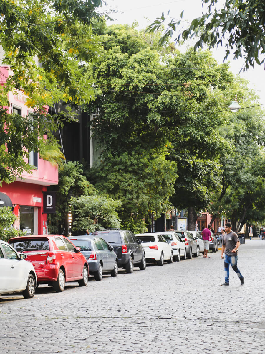 A man crosses a cobblestone street lined with parked cars below a canopy of trees in Palermo Soho Buenos Aires