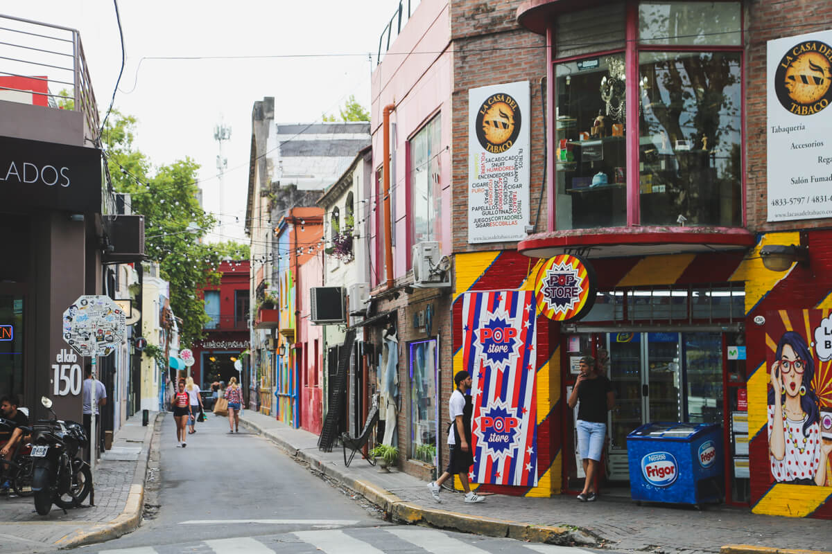 An alleyway is painted in colorful murals and decorated with edison lightbulbs in Buenos Aires Palermo Soho