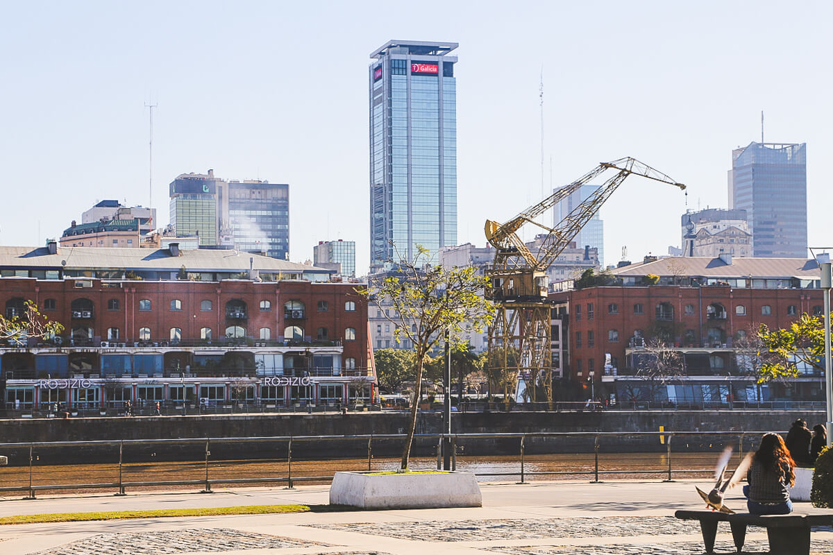 A woman sits on a bench overlooking the water, a crane, and red brick warehouses in Puerto Madero Buenos Aires