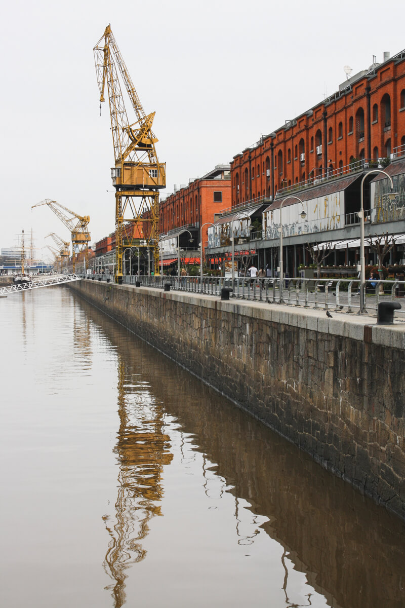 A crane and red brick warehouses stand next to the water at the modern Buenos Aires port neighborhood Puerto Madero