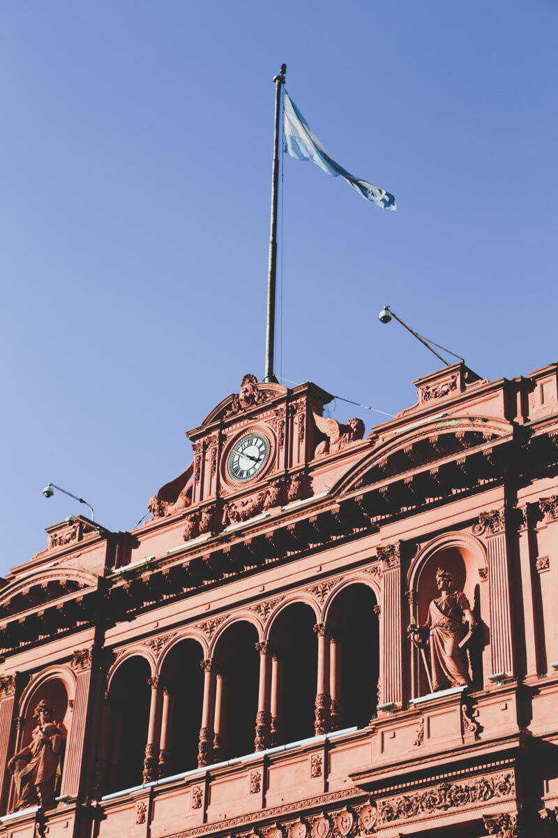 A pink facade of an old mansion in Buenos Aires with a clock and flag stand against a bright blue sky