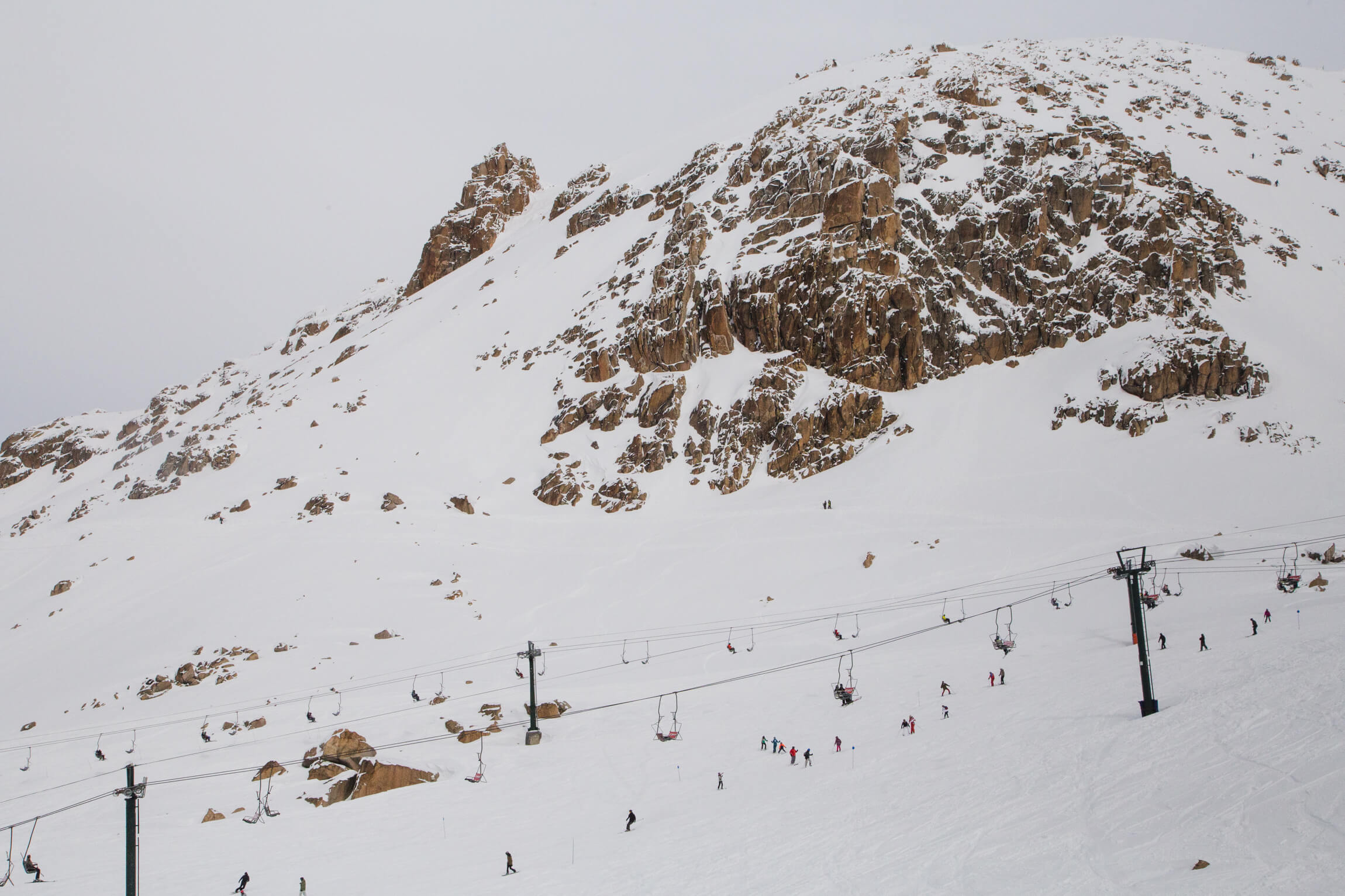 A snow covered mountain is covered with skiiers and snowboarders in Bariloche in Winter