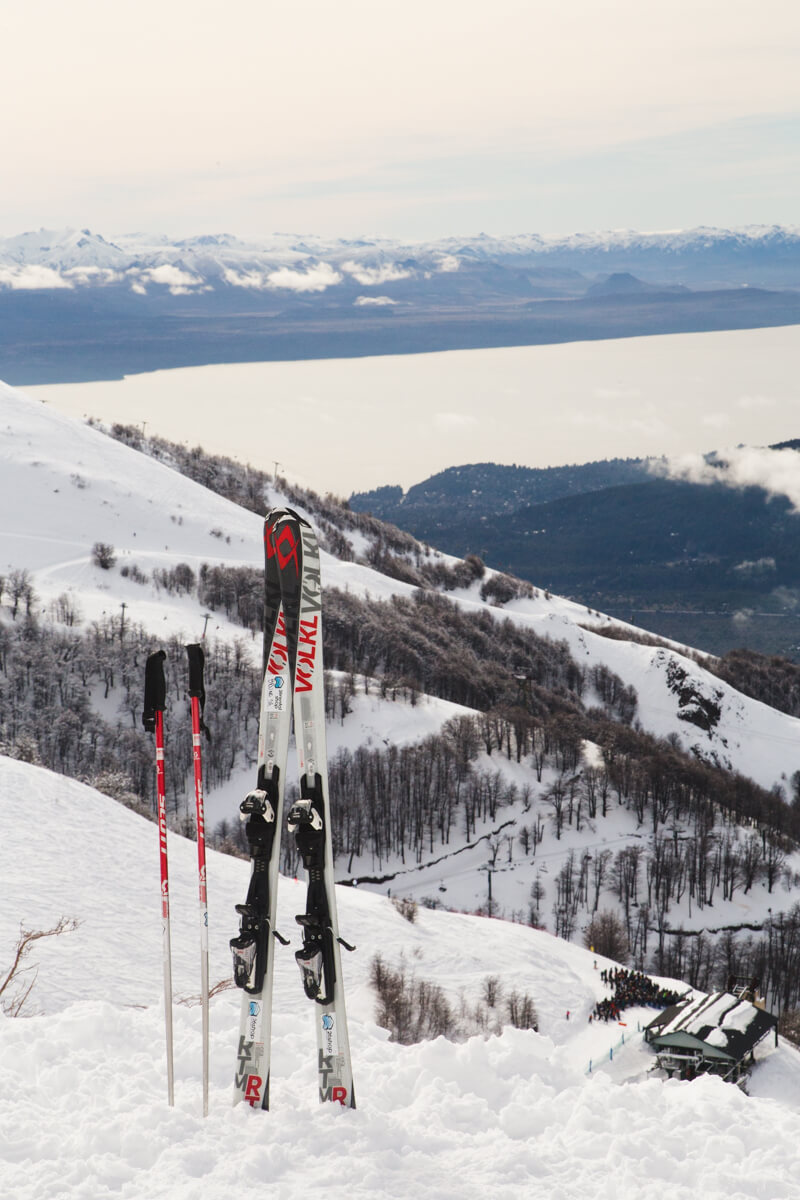 Two skis stand up in the snow with a panoramic view of a lake and snow covered mountains in the background in Argentina