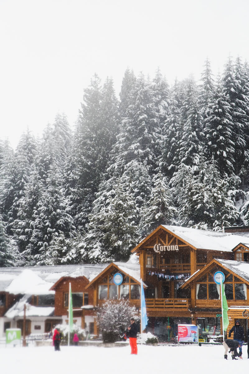 Wooden buildings housing ski gear rentals and restaurants stand in the snow in front of a forest of pine trees.