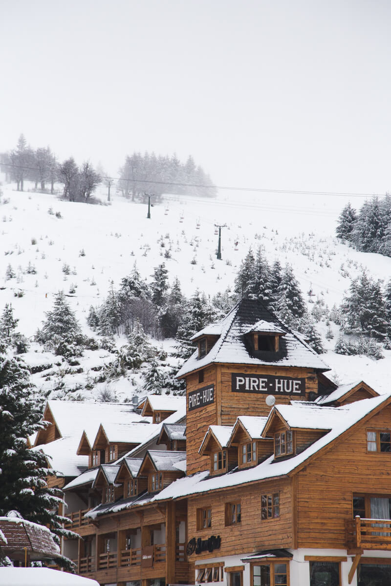A wooden building, a hotel and restaurant, in front of a snow covered mountain at the Cerro Catedral Ski Resort