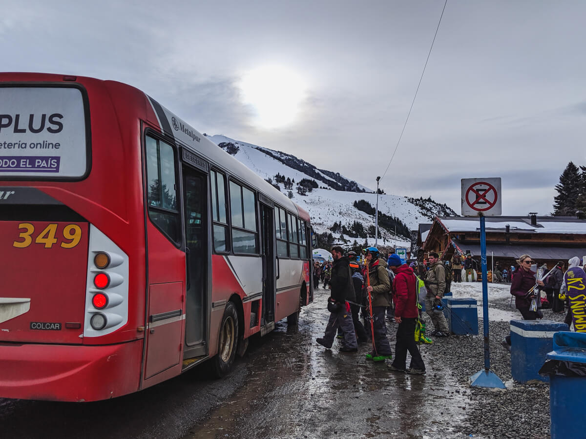 Men with skis and snowboards board a red public bus in at the Bariloche ski resort
