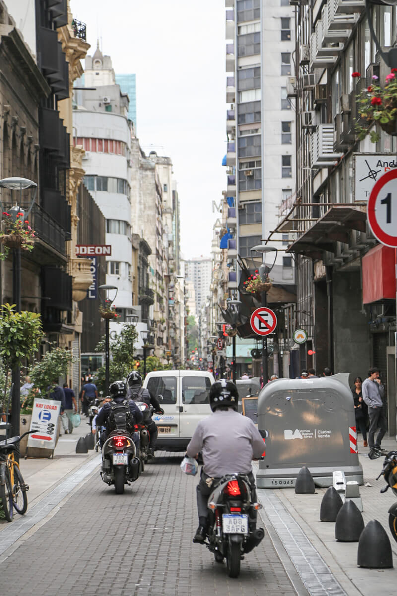 Three men on motorcycles drive down a paved road in busy Buenos Aires