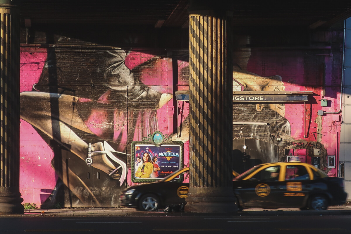 Two black and yellow taxis drive under a bridge in front of a hot pink mural of tango dancers in Buenos Aires
