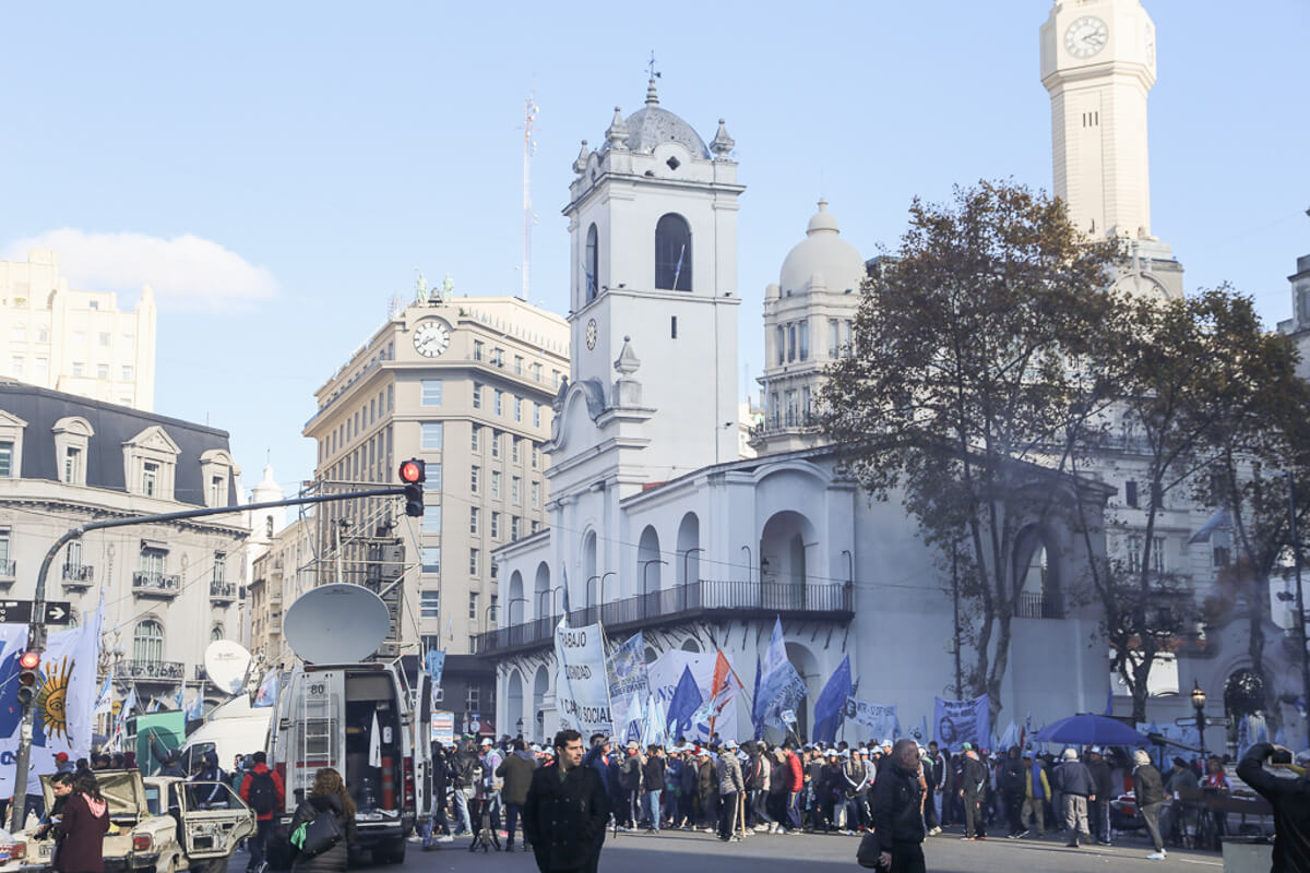 A workers union protests in Plaza de Mayo in Buenos Aires with flags and signs in front of a news crew filming them.