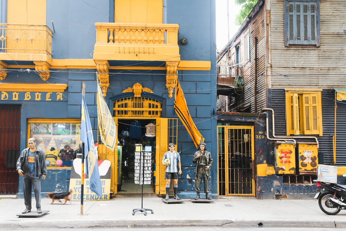 Blue and yellow buildings with statues of Argentine sports figures in La Boca Buenos Aires