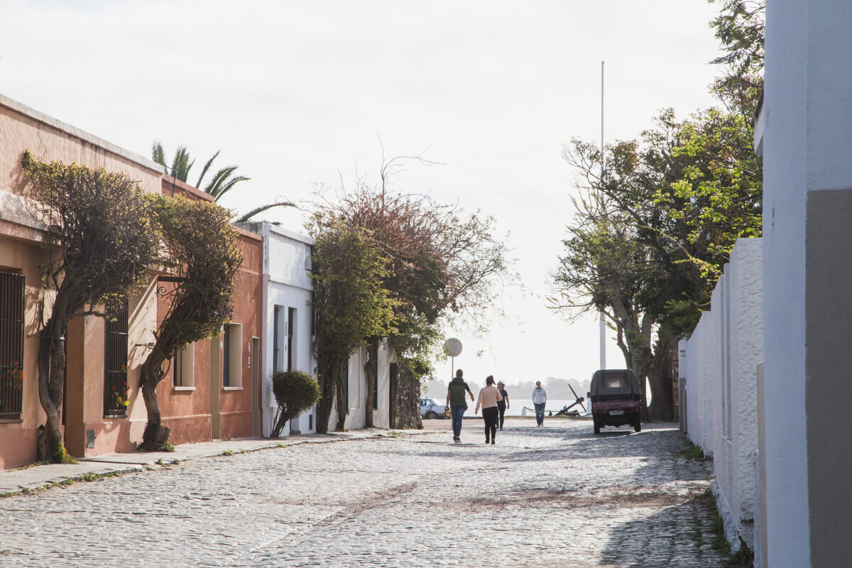 People in the distance walk down a cobblestoned street lined by historic one story homes on a Colonia del Sacramento day trip