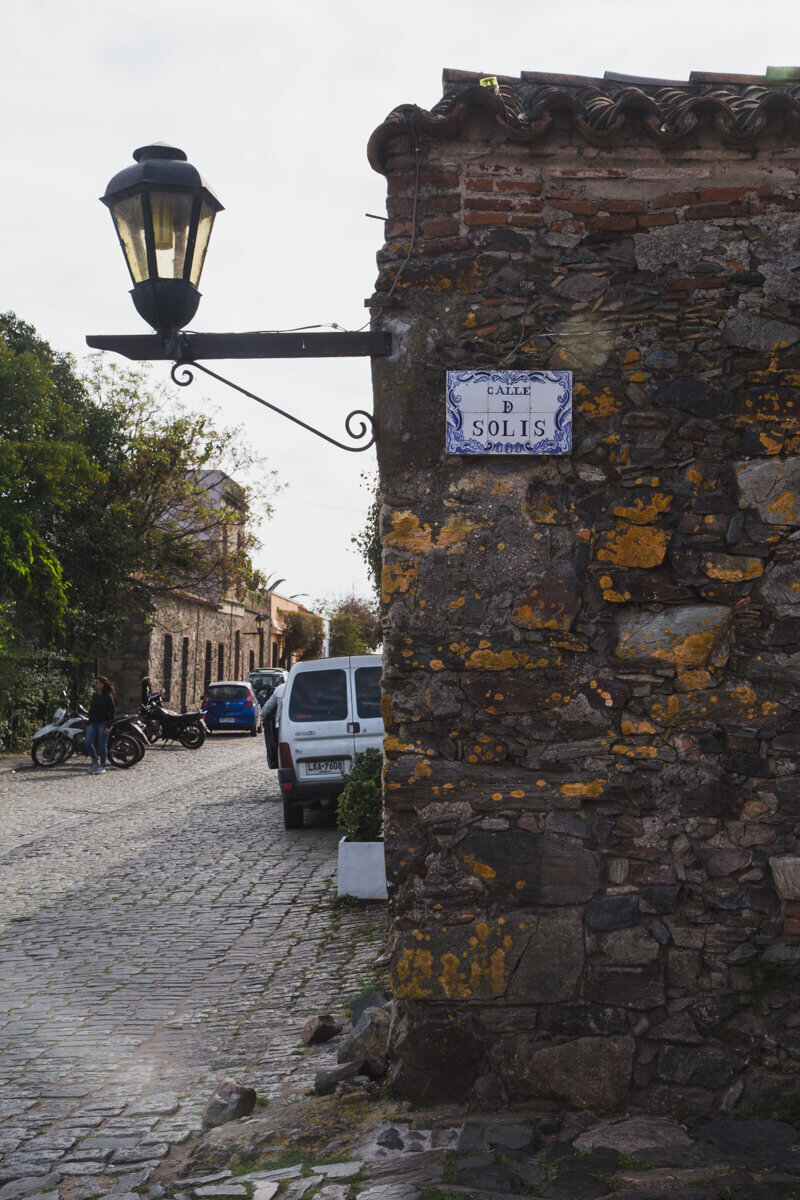 A brick and stone street corner on a cobblestone street with an antique street light in Uruguay
