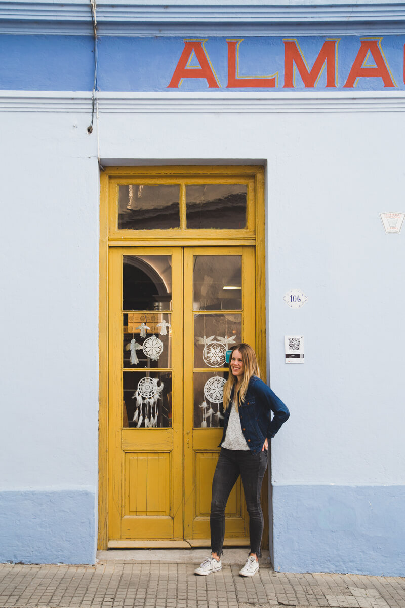 A woman stands in front of a yellow door in a blue building in Colonia del Sacramento Uruguay