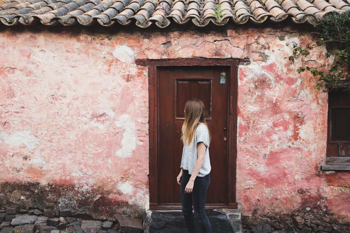A woman stands in front of a red stucco building from the 17th century while on a Colonia day trip