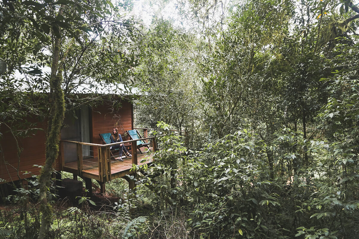 A girl sits on a deck in a tree house at one of the best hotels in Argentina in the Misiones jungle