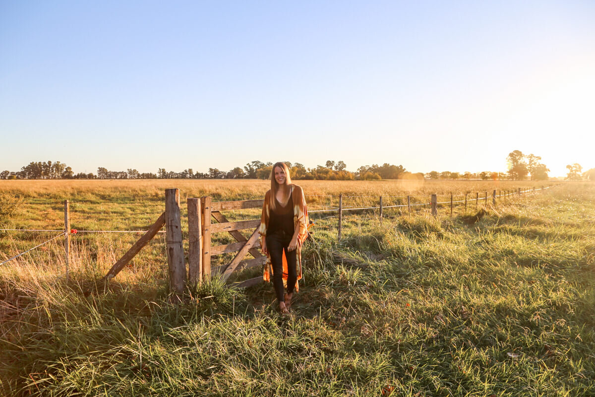 A woman standing in a pasture as the sun sets in one of the best estancia hotels in Argentina