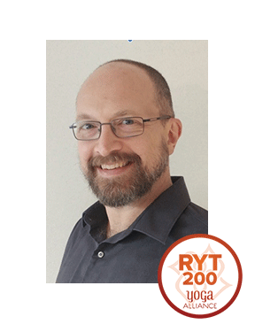 """Troy Pyles, RYT 200, AHC Troy is a Registered Yoga Teacher who studied at Yoga on High and an Ayurvedic Health Consultant. He is a cancer survivor who found a path to wellness using Yoga, Reiki, Ayurvedic lifestyle practices and alternative therapies. As a full-time engineer working in a manufacturing environment, Troy understands the everyday challenges of finding balance alongside the stresses of modern life. He enjoys teaching pranayama, yoga and mindfulness """"off the mat"""" and feels that they should be applied in a practical way as part of everyday life."""