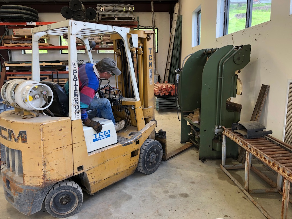 Bill gently picks up the press break to move to the other side of the shop