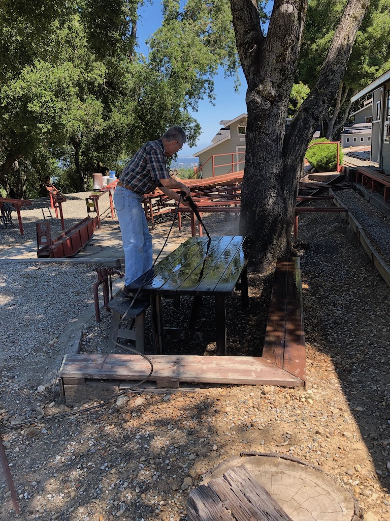 Ken power washes the tables in advance of the June run