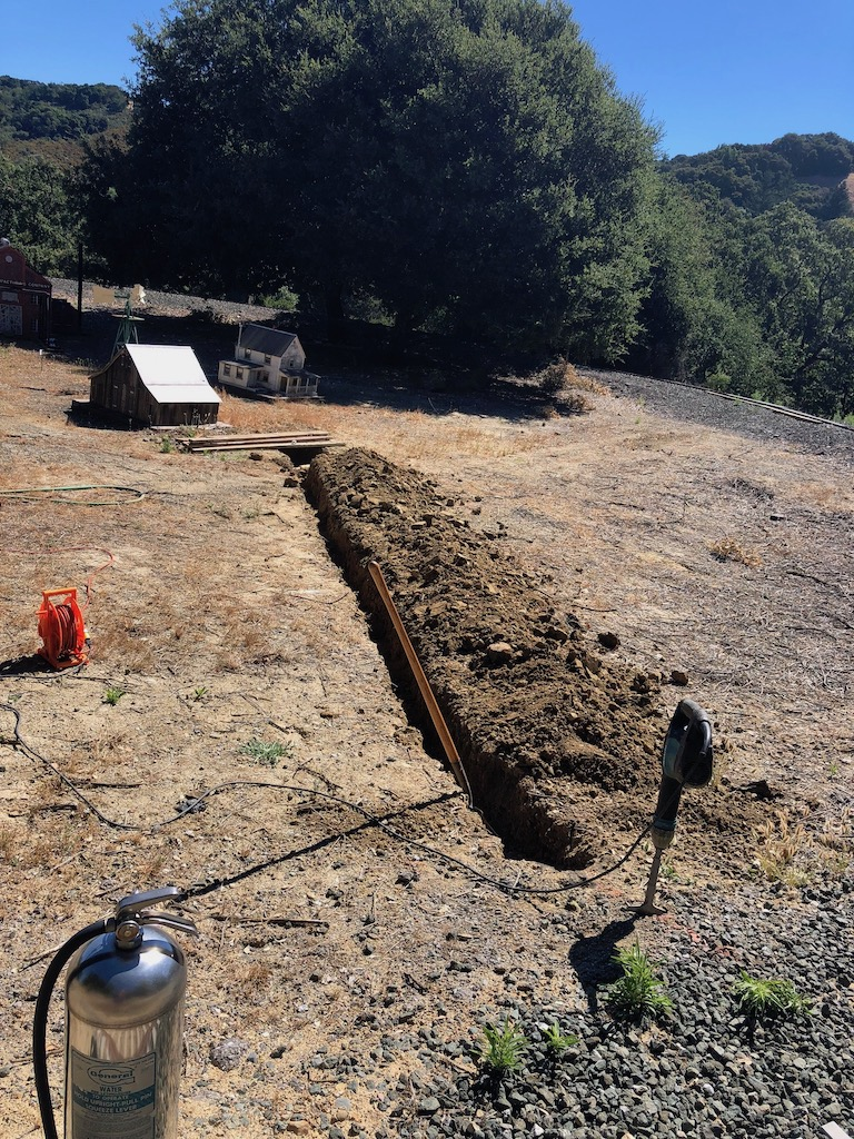 Bruce and Russ dug a trench for the water line to move the sprinkler closer to the hillside.