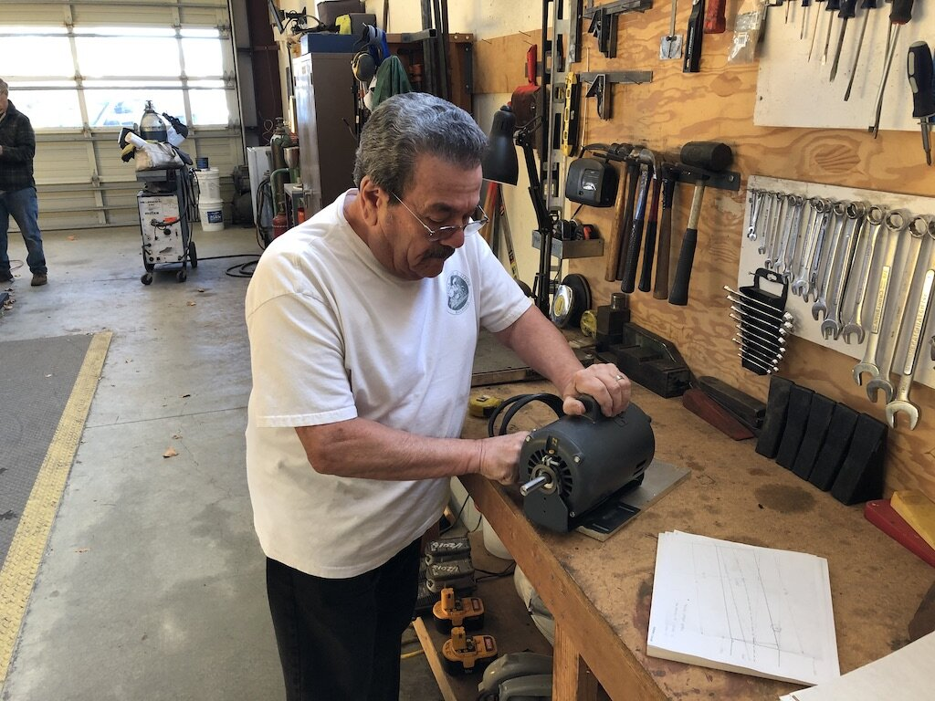 Carl mounting a donated motor for a new steel brush deburrer