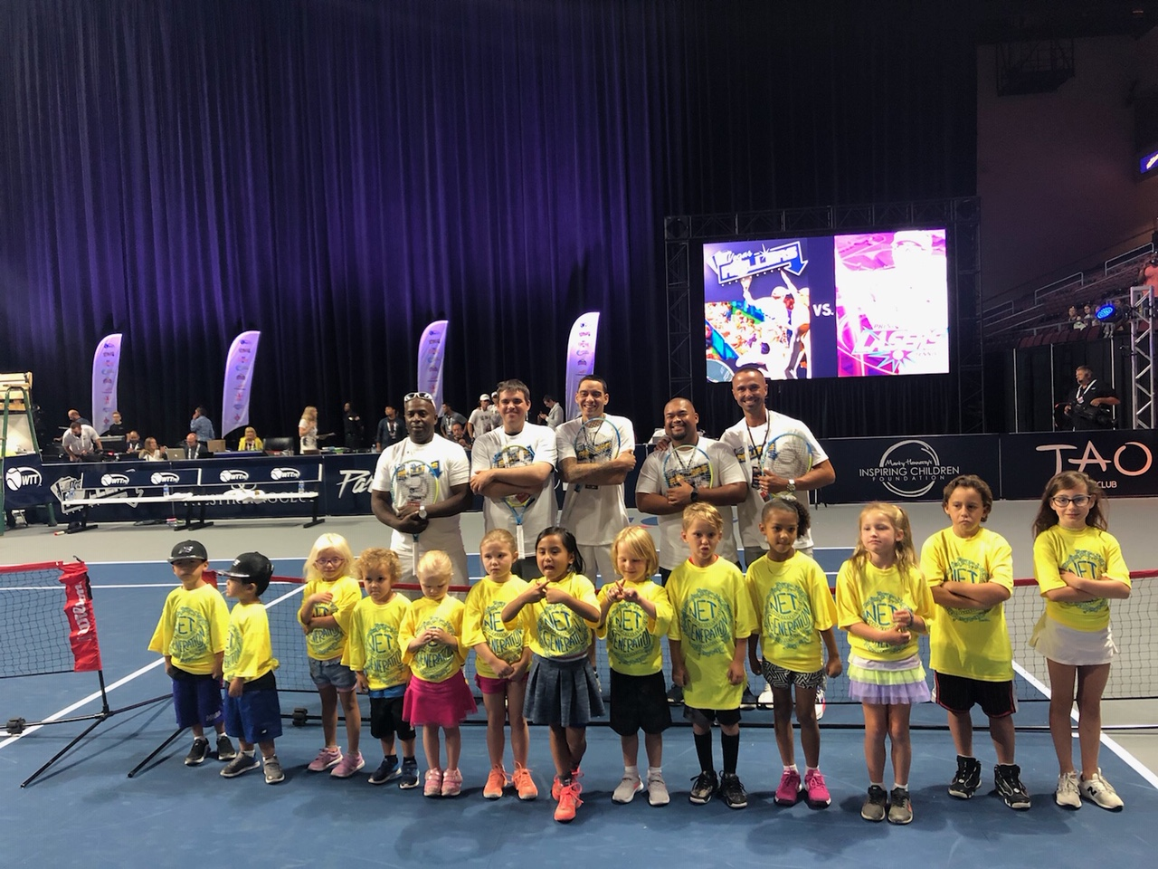 USPTA U30 Volunteers Offer Clinic in Las vegas - USPTA Intermountain Division VP & U30 Lead Karl Jones and USPTA U30 Professionals Rudy Abitago and Jake Lysgaard with kids at World Team Tennis in The Orleans Arena, Las Vegas, Nevada. The Las Vegas Rollers took on The Springfield Lasers in front of a sold out crowd.U30 Professionals provided a clinic for kids on the WTT court ahead of the home opener for Las Vegas, enjoying their first season with a WTT tennis team.