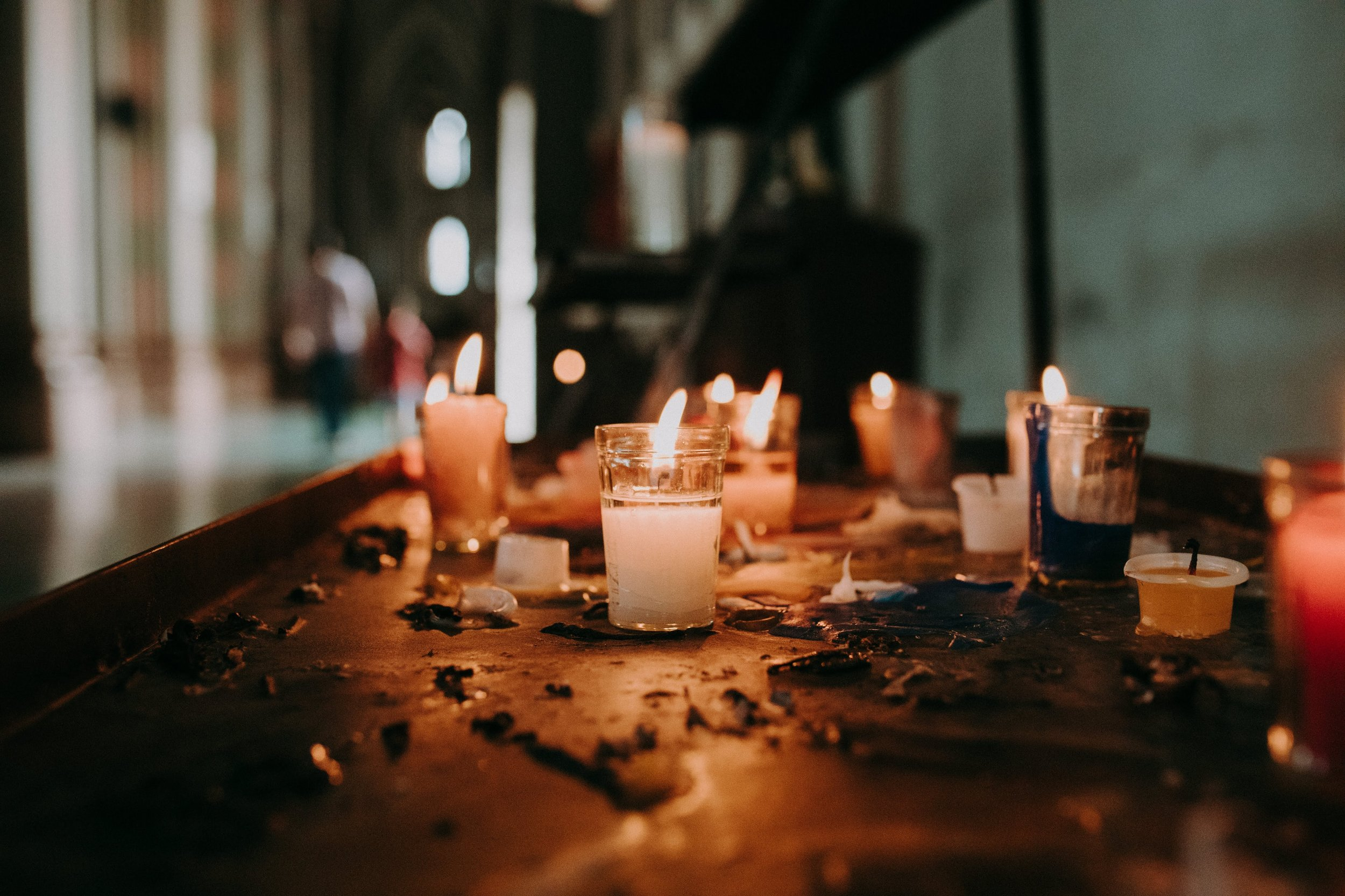 A collection of small candles flickering on a table.