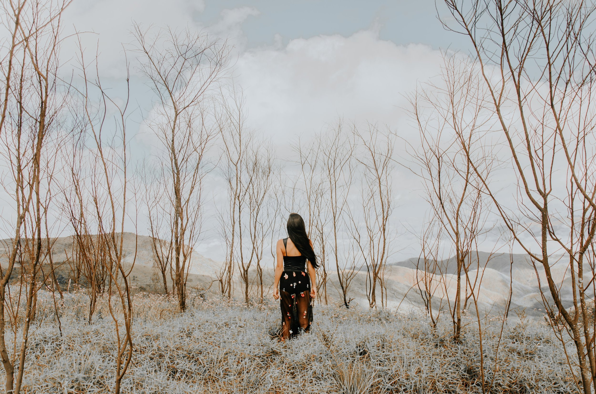 Young woman with long black hair and a black dress walking through a scrubby desert.