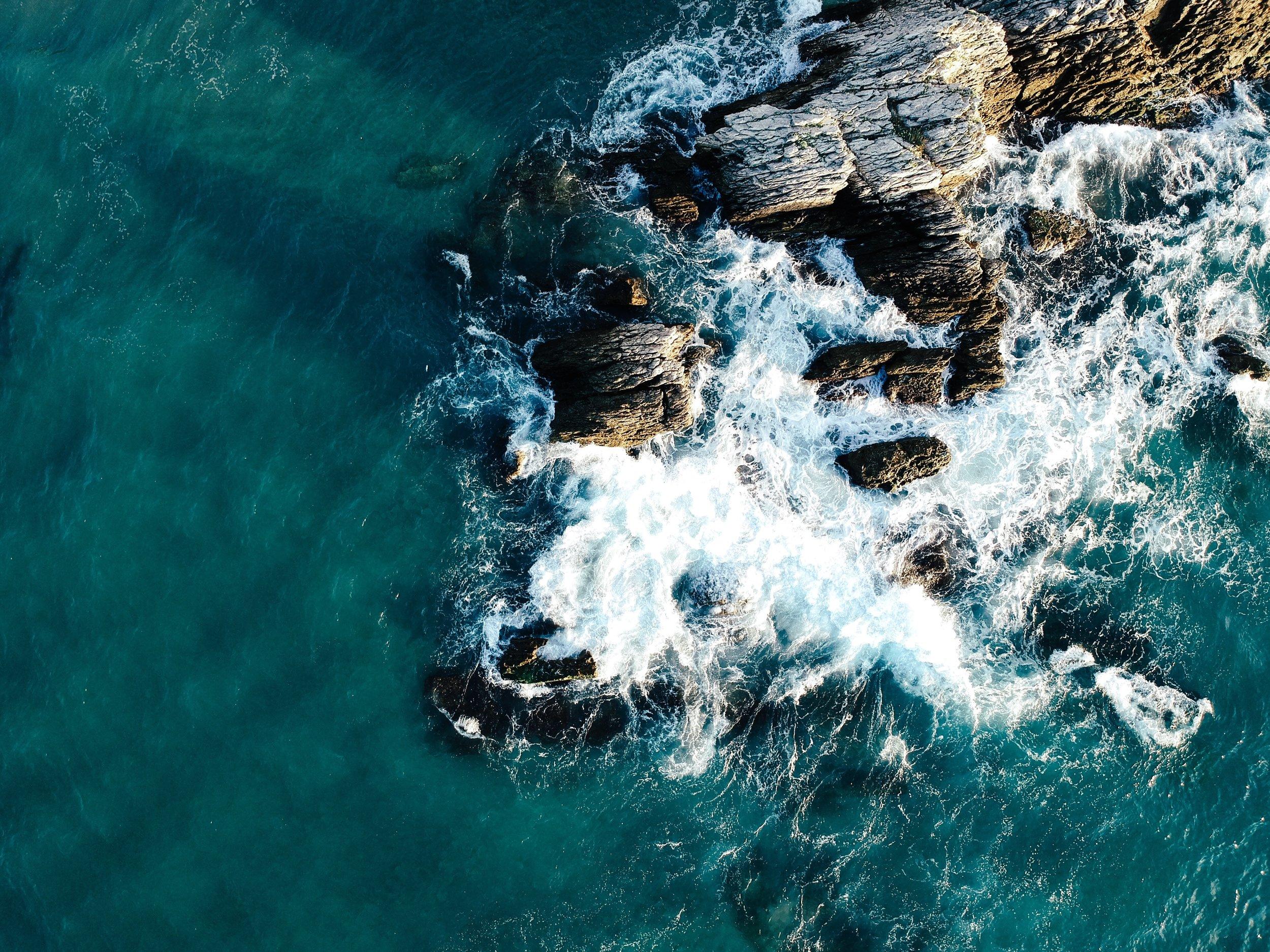 Dark teal ocean with waves crashing up against rocks.