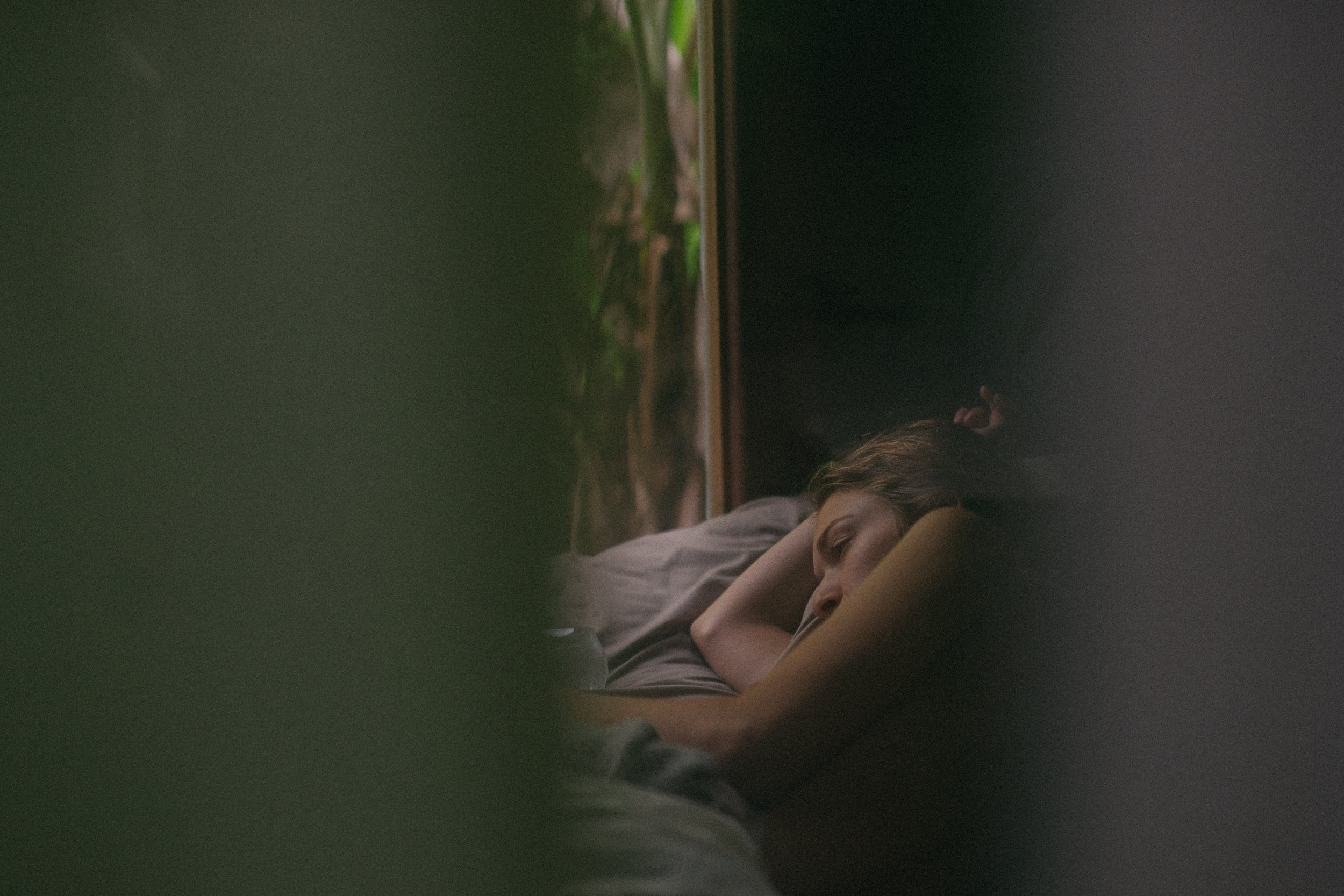 Framed through an open door, a young woman is laying in bed with her eyes open.