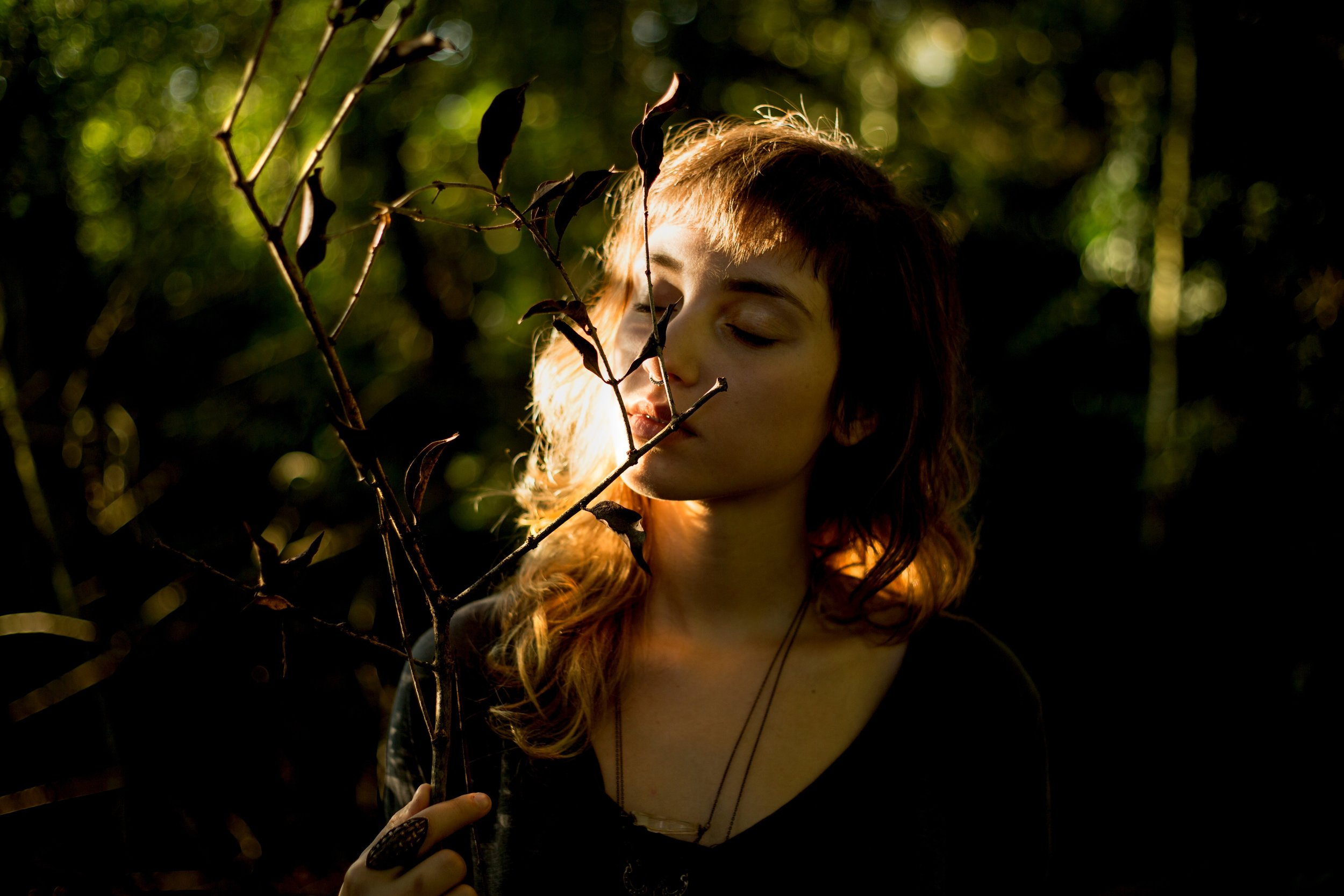 A young woman in a forest with her eyes closed, holding a branch in front of her face.