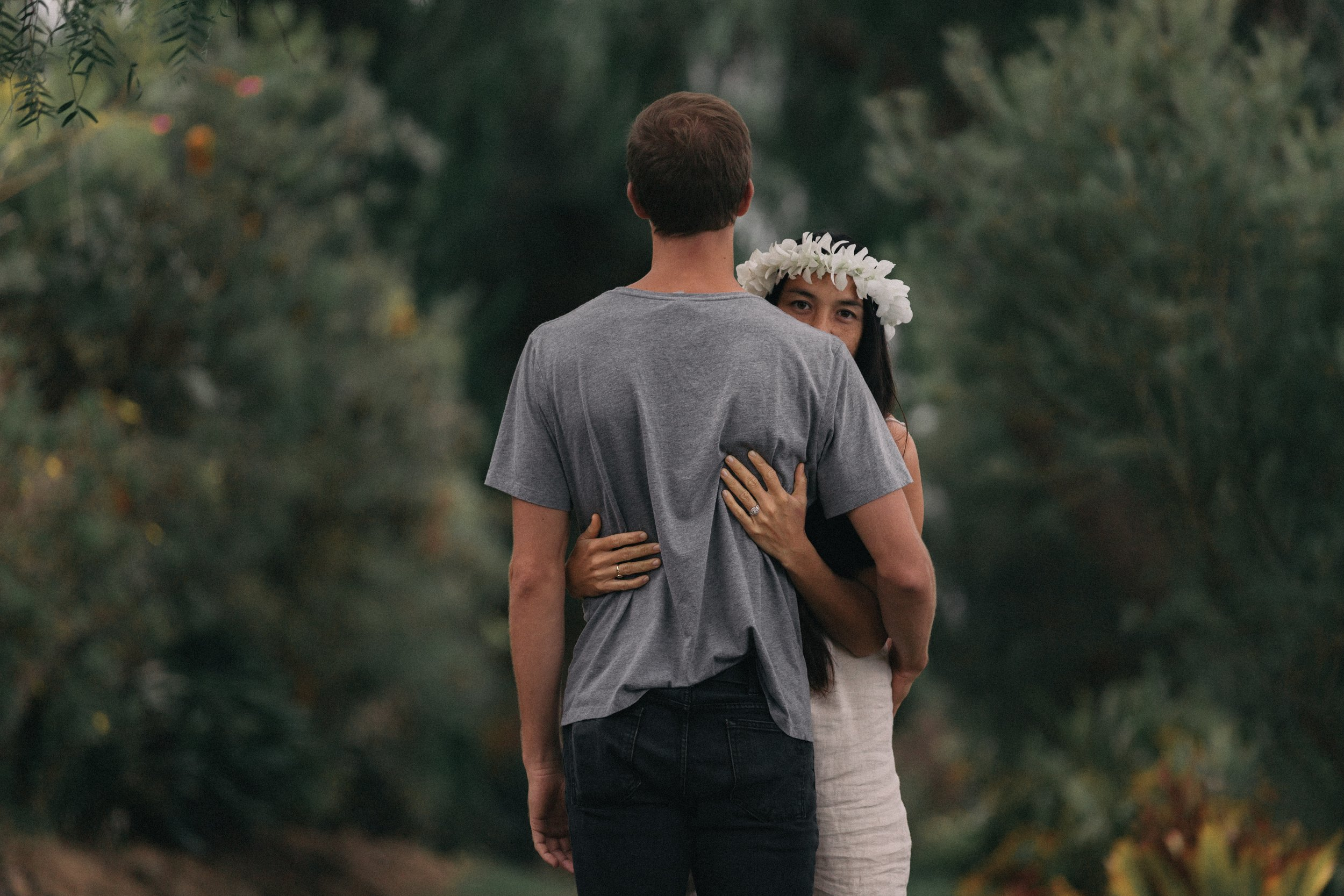 A girl and a boy embracing. The girl is wearing a white flower crown, and has an engagement ring.