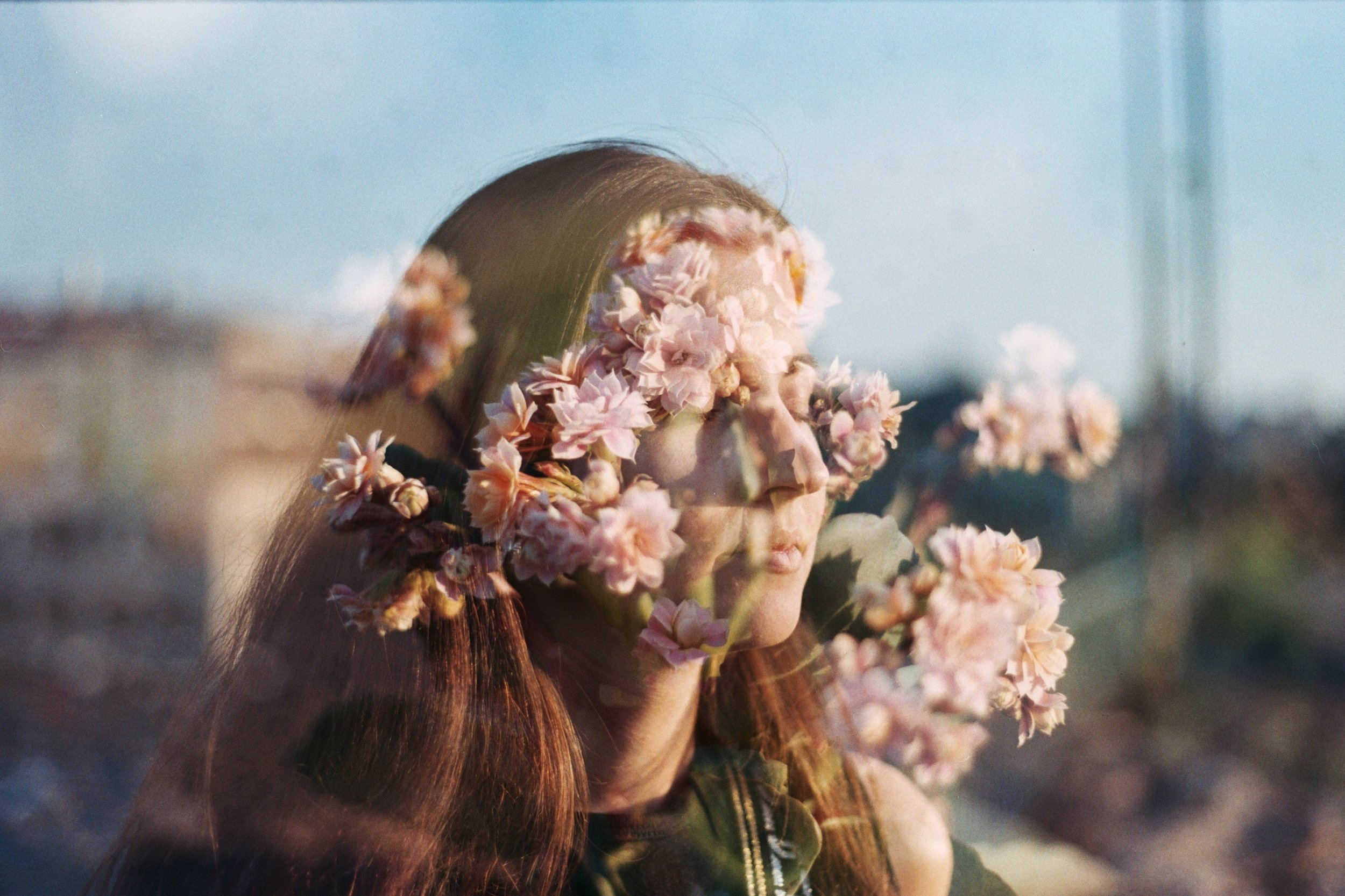 Double-exposure photo of a young woman and blooming pink flowers.