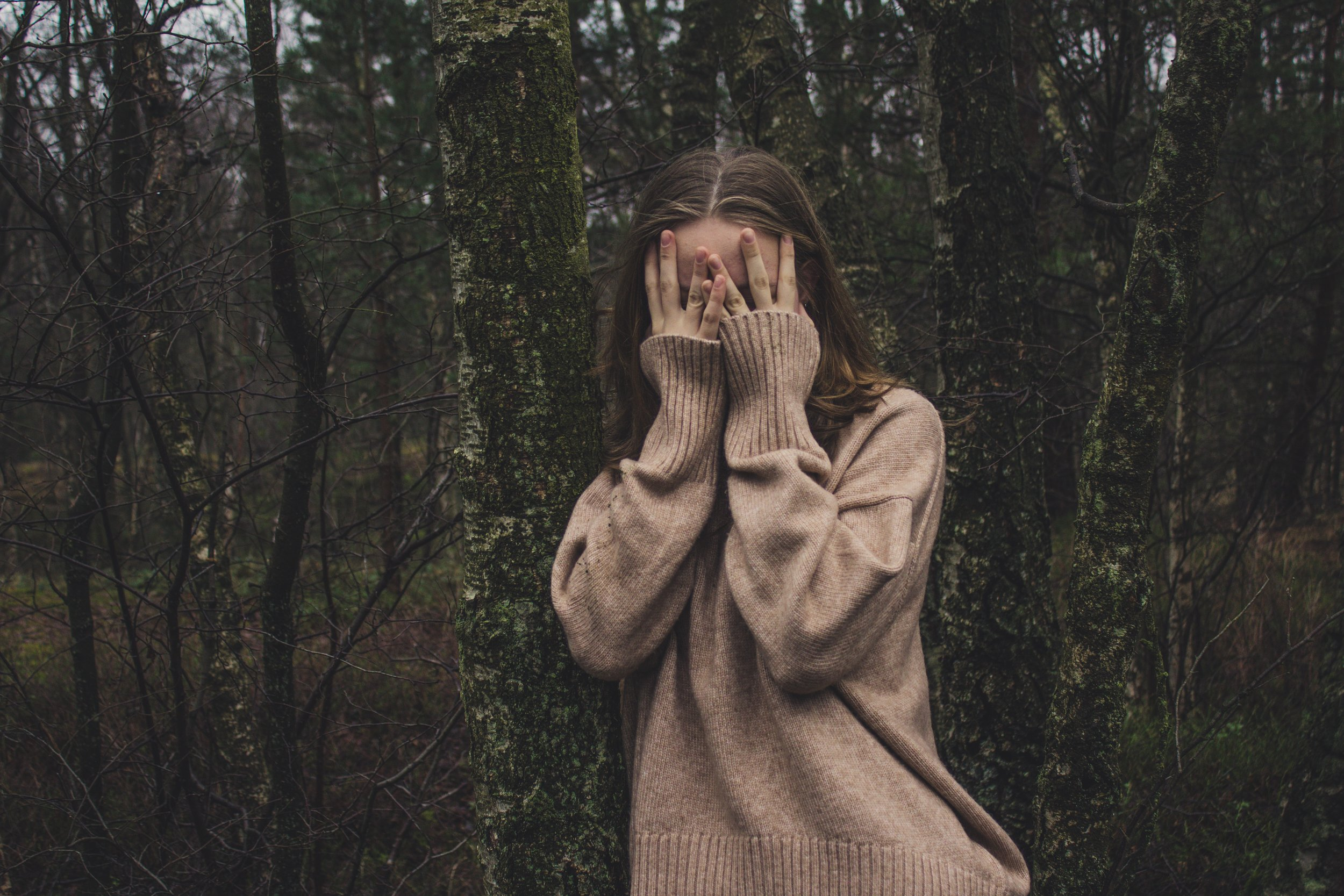A young white woman in an oversized brown sweater stands in a forest, her hands covering her face.