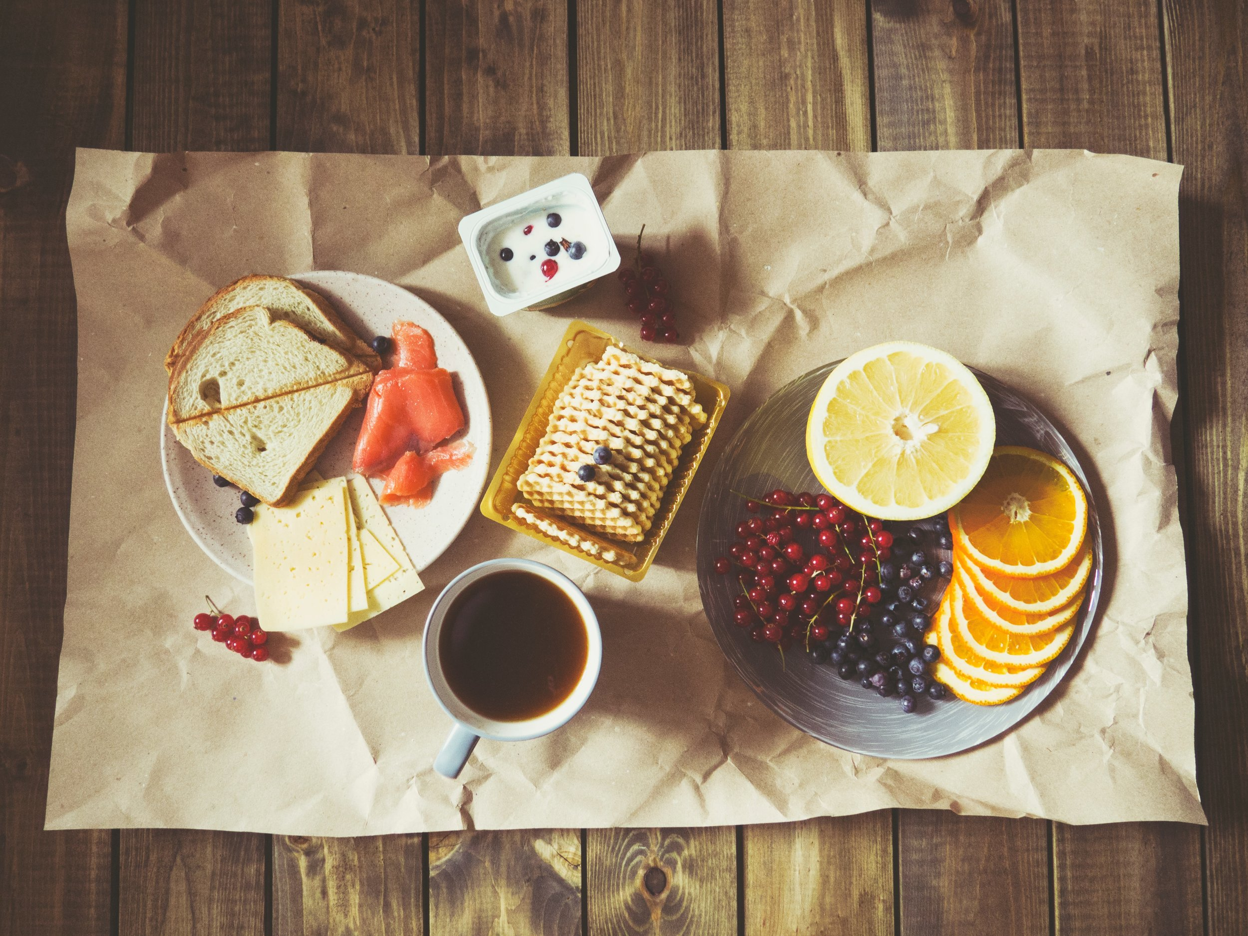 Cheese, crackers, fresh fruit, and a mug of tea spread out on a table.