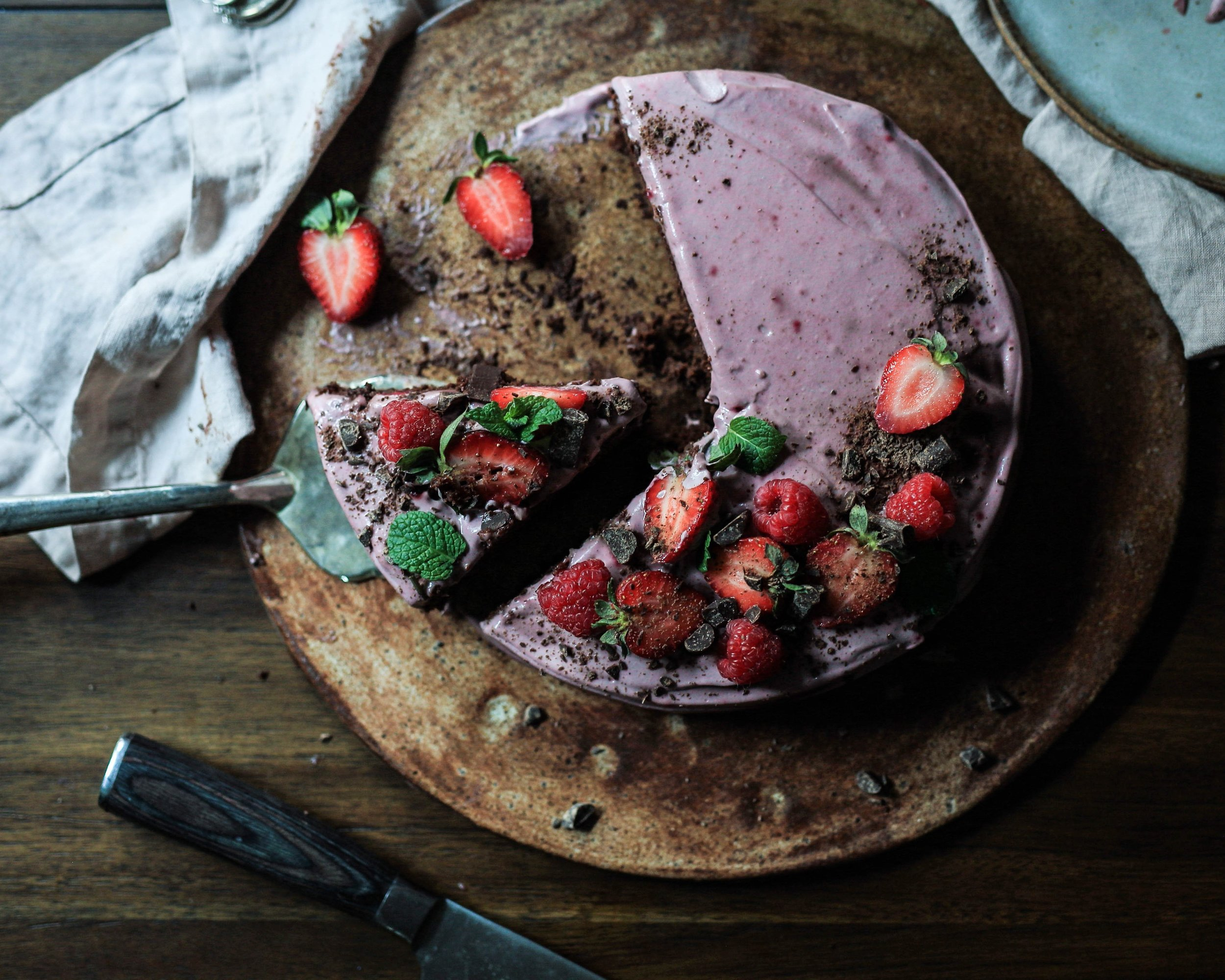 Homemade cake with purple frosting and fresh strawberries.