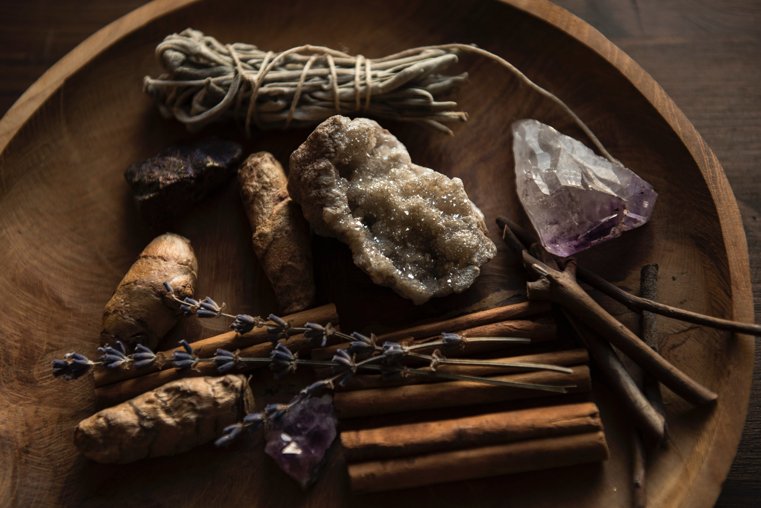 Herbs and crystals on a wooden platter.