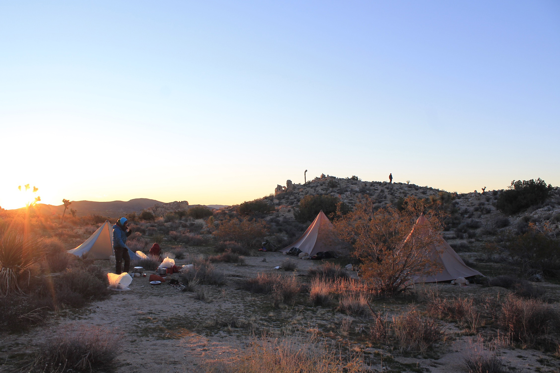 Outward Bound instructor passing by campsite during sunset.