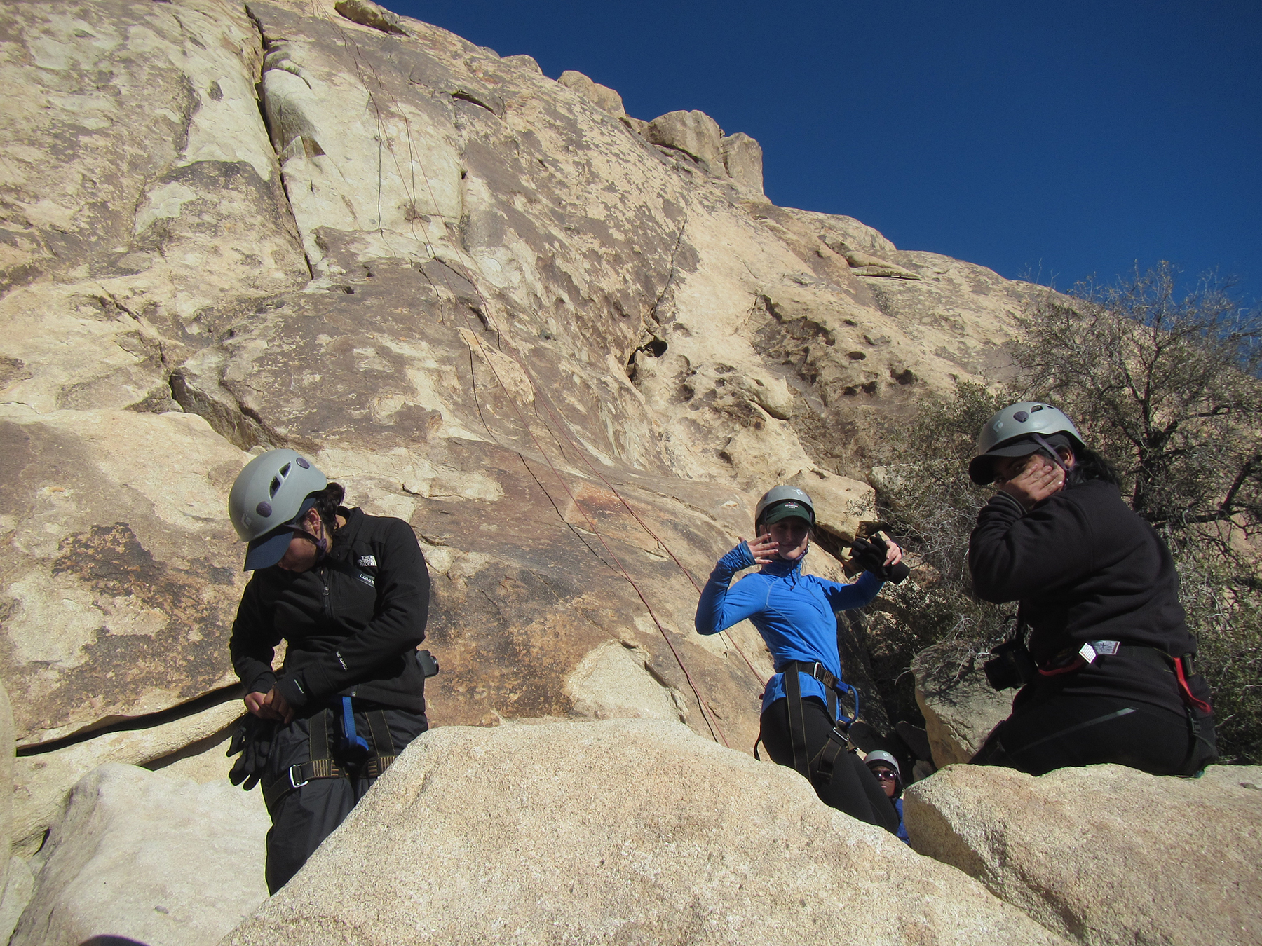 Ingrid, Jamie, and Behtsabe checking harnesses before their climb.