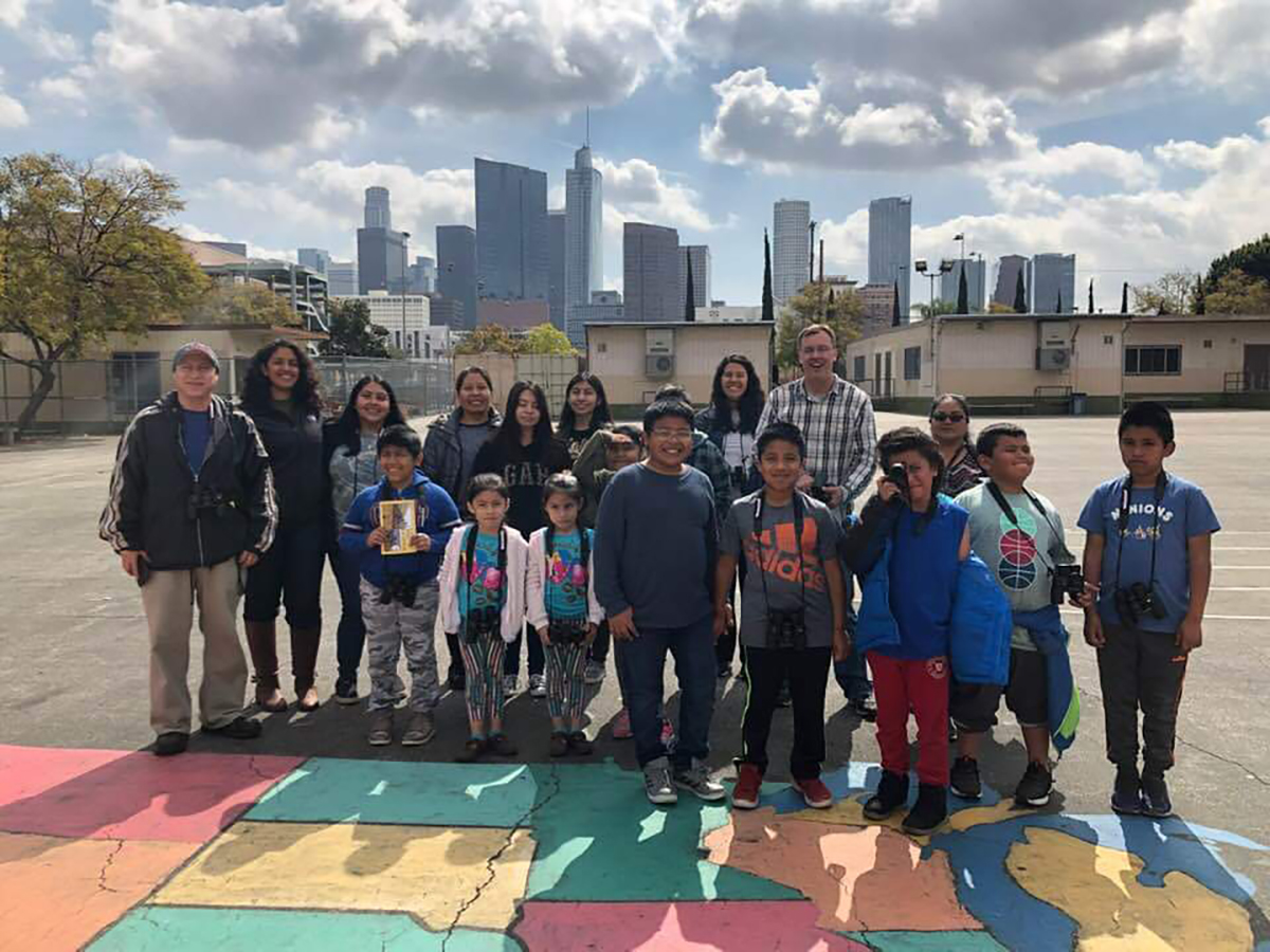 Esperanza families, the principal, Brad Rumble, ee360 interns and students pose in front of DTLA after receiving their calendars.
