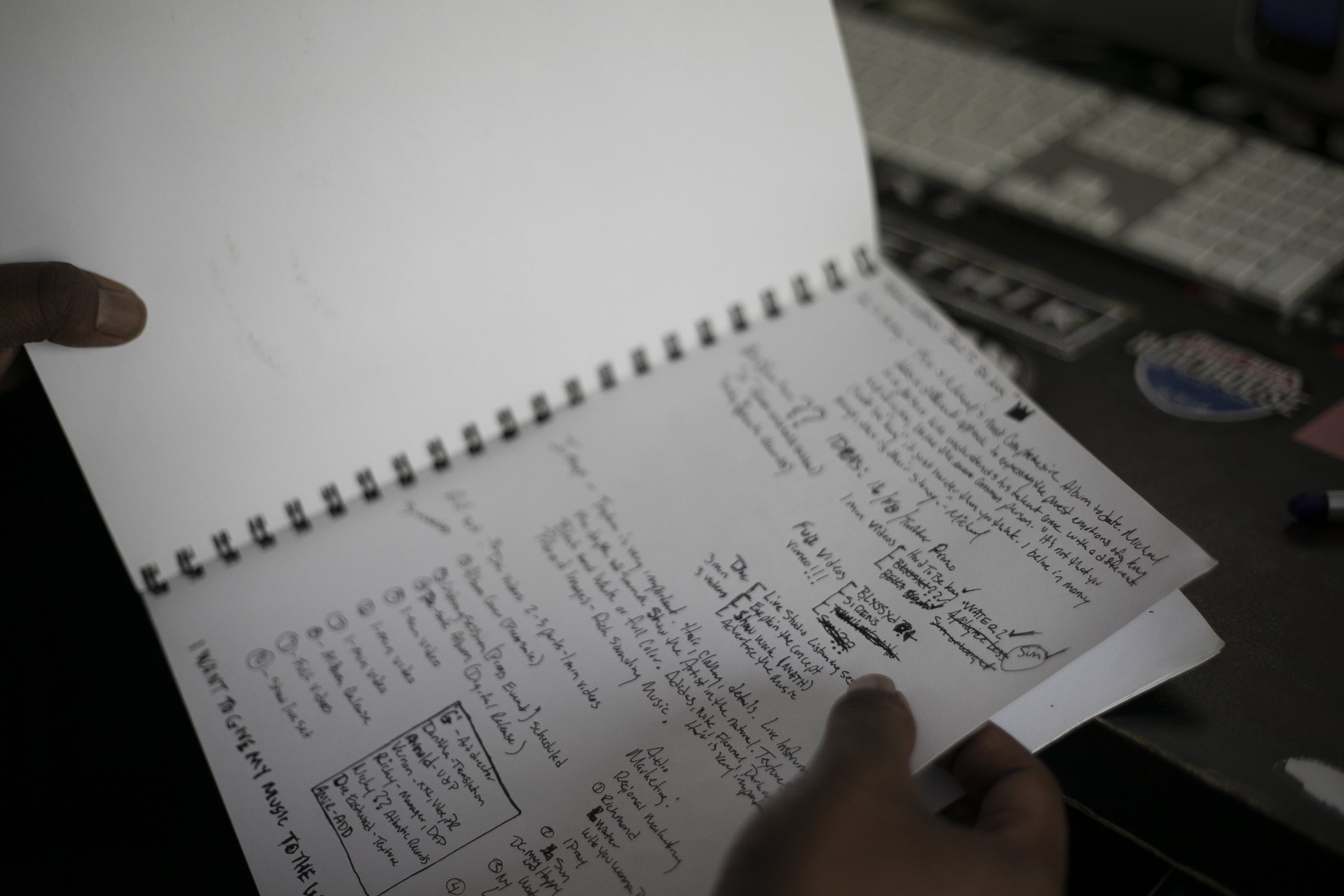 "Mike thumbs through an old notebook on April 24, 2019 in Richmond, Virginia. Mike also co-founded, alongside his brother Brandon Bass, the record label Purple Republic Music Group. He his heavily involved in all aspects of music, including the business side. This page is the rollout plan for his most recent project ""Hard to be King."""