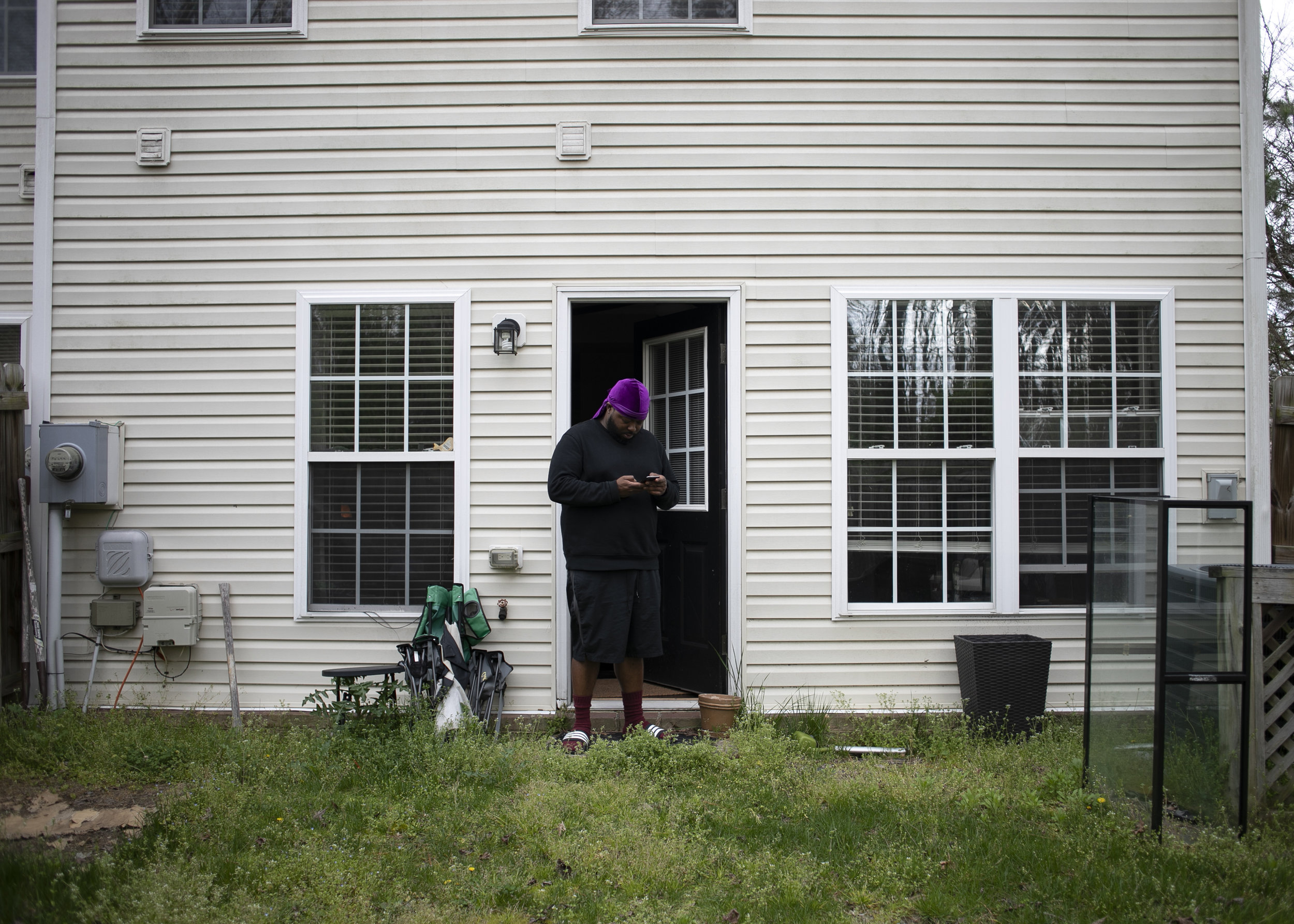 Mike stands at the back door of his house while answering a text and getting some fresh air on April 7, 2019 in Richmond, Virginia.